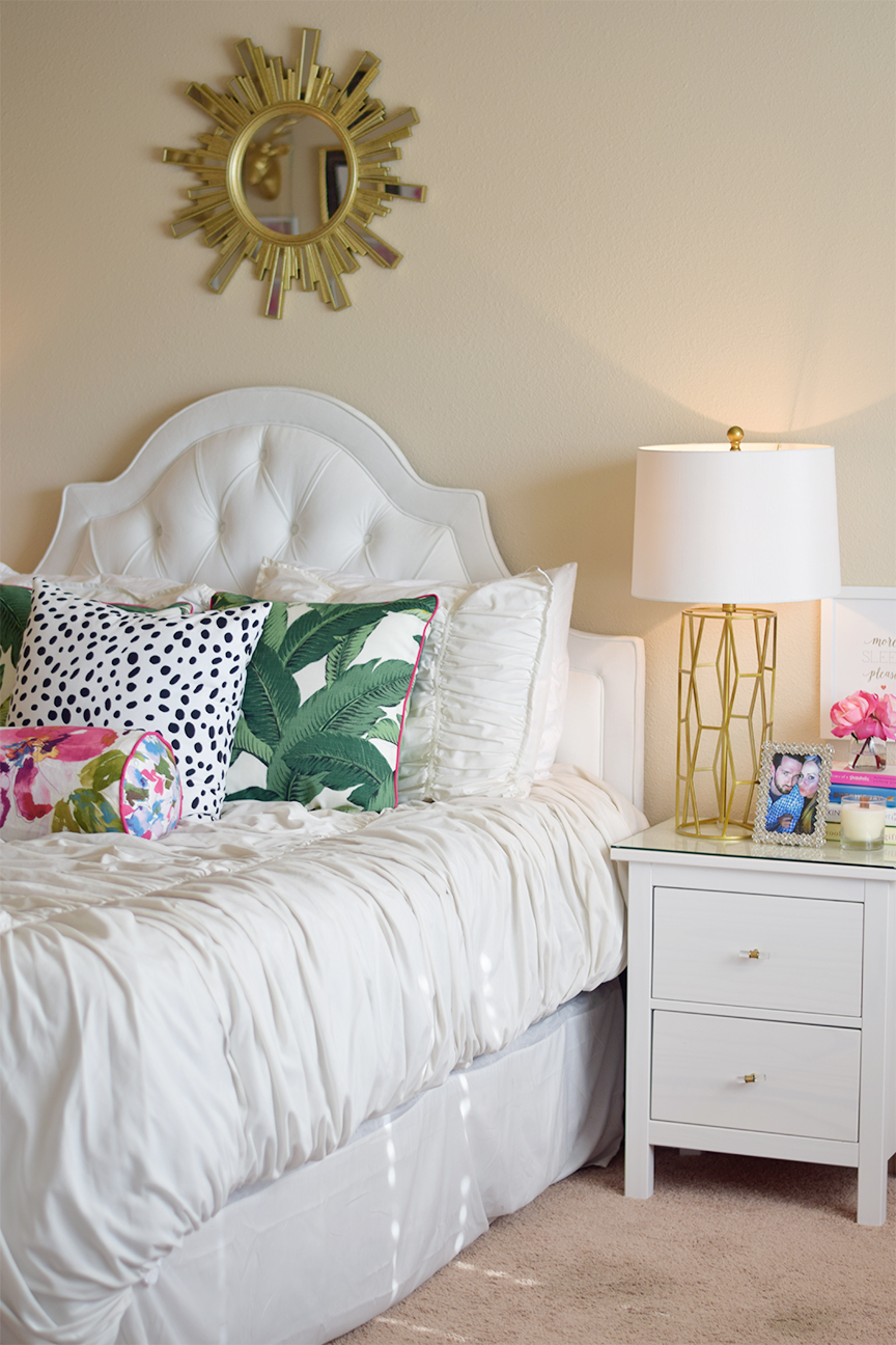 white tufted headboard and palm leaf pillows
